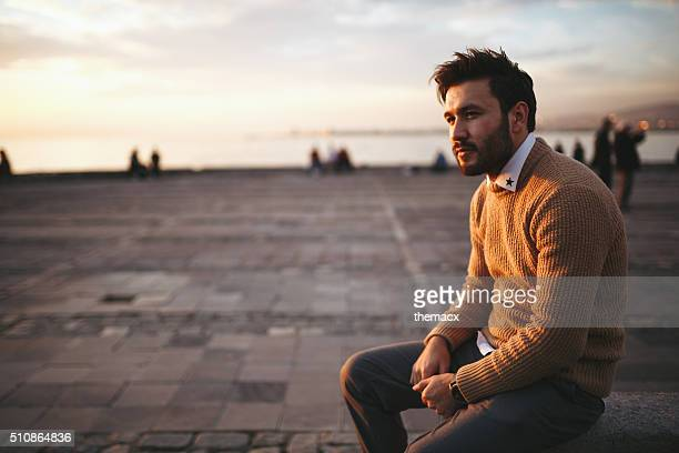 Young man sitting looking away