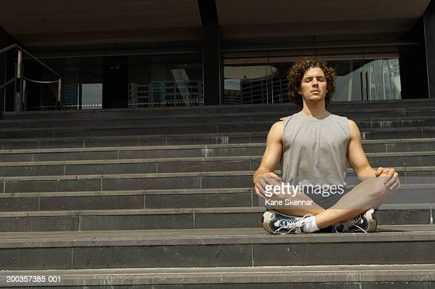 Young man sitting meditating on steps