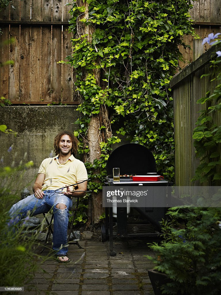 young man sitting next to barbecue in backyard stock photo getty