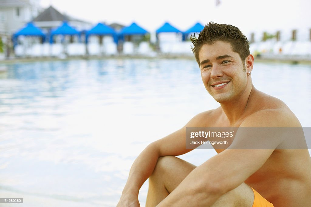 Young man sitting next to swimming pool : Stock Photo