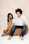Young man sitting on a bean bag using a laptop with a young woman sitting beside him talking on a mobile phone