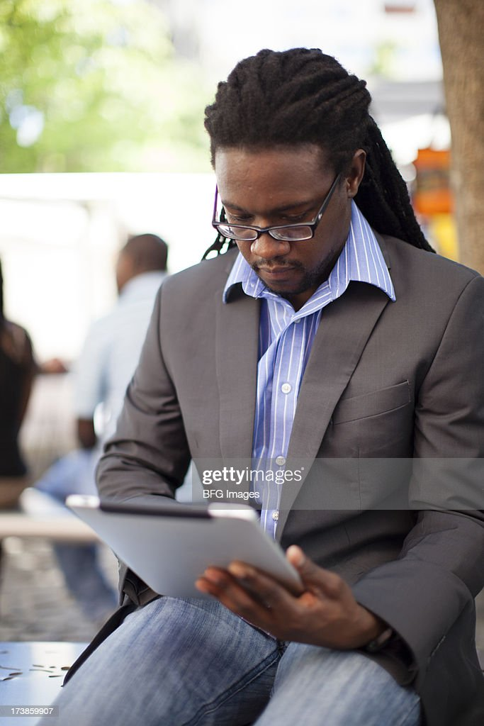 Young man sitting on a bench outdoors working on his digital tablet. Cape Town, Western Cape Province, South Africa : Stock Photo