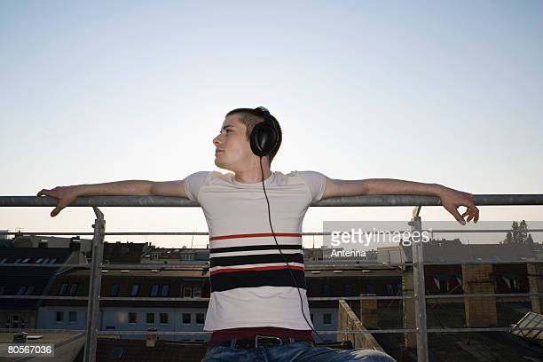 A young man sitting on a rooftop wearing headphones