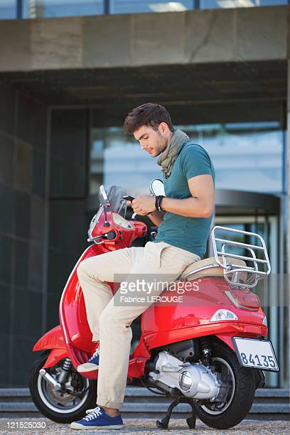 Young man sitting on a scooter and text messaging