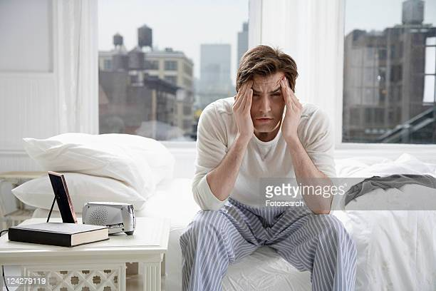Young man sitting on bed and rubbing forehead