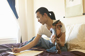 Young man sitting on bed, composing music, holding violin