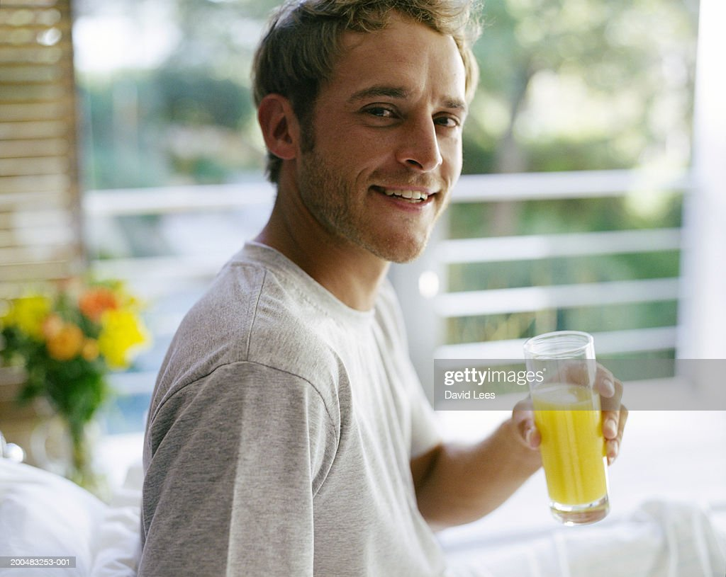 Young man sitting on bed, holding glass of orange juice, portrait : Stock Photo