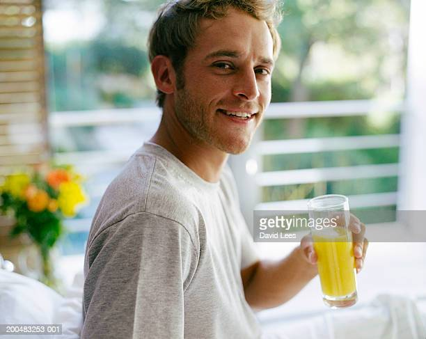 Young man sitting on bed, holding glass of orange juice, portrait