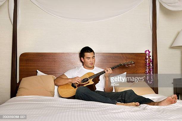 Young man sitting on bed playing guitar