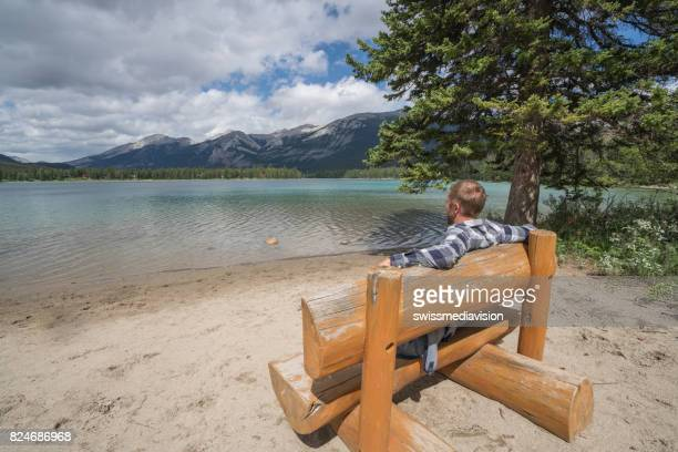 Young man sitting on bench by the lake