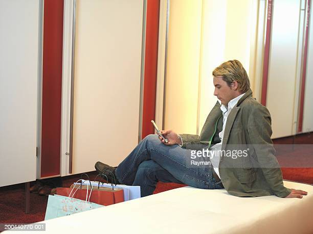 Young man sitting on bench in dressing room using mobile phone