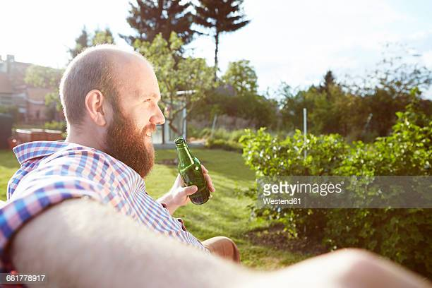 Young man sitting on bench in garden, drinking a beer