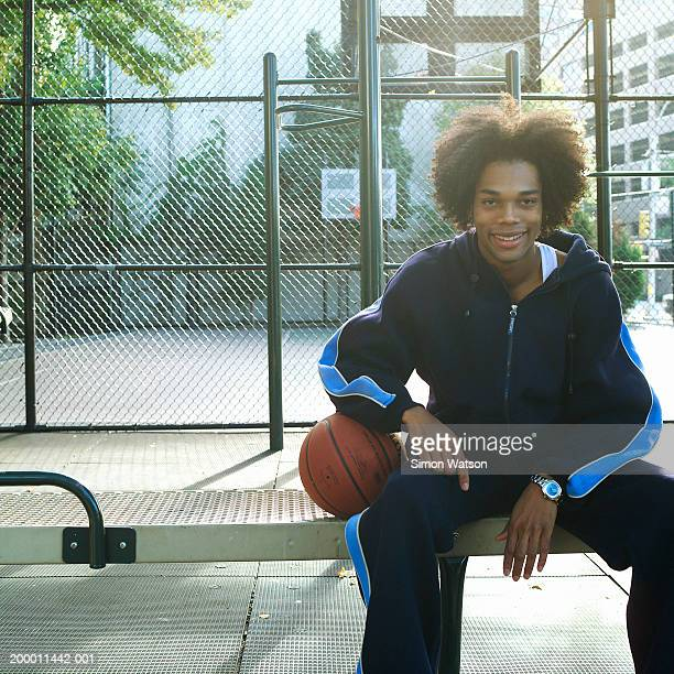 Young man sitting on bench with basketball, portrait