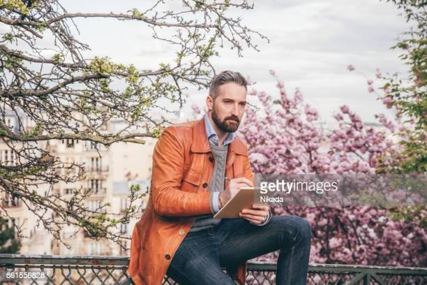 Junger Mann sitzen auf Bank mit Sketchbook, Montmartre, Paris