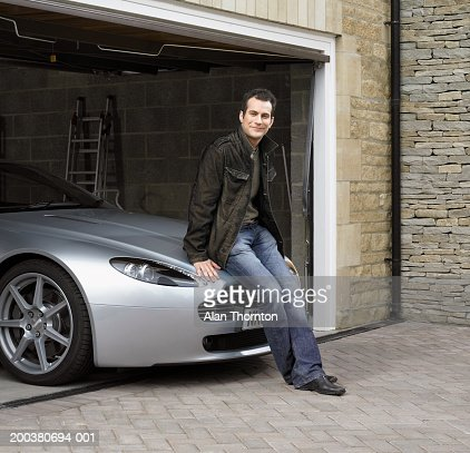 Young man sitting on car in garage, smiling, portrait : Stock-Foto