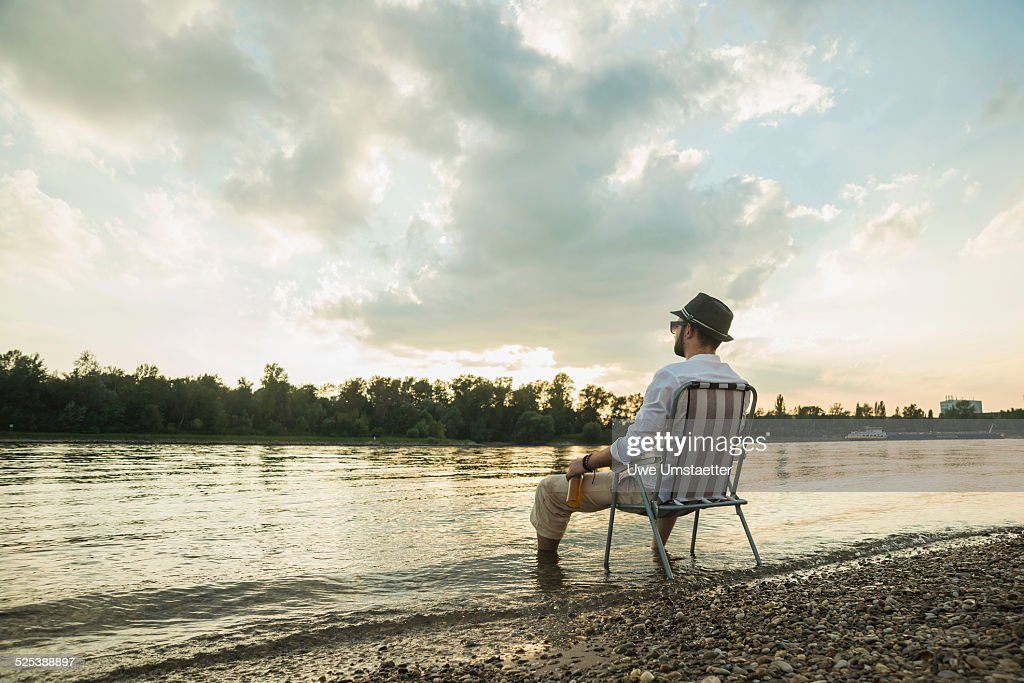 Young man sitting on chair by lakeside