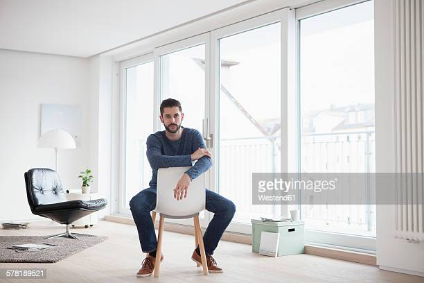 Young man sitting on chair in his living room