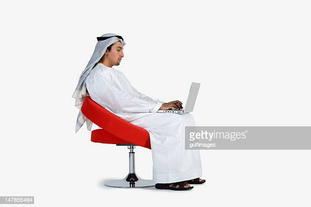 Young man sitting on chair, using laptop