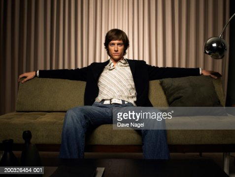 young man sitting on couch portrait stock photo getty images. Black Bedroom Furniture Sets. Home Design Ideas