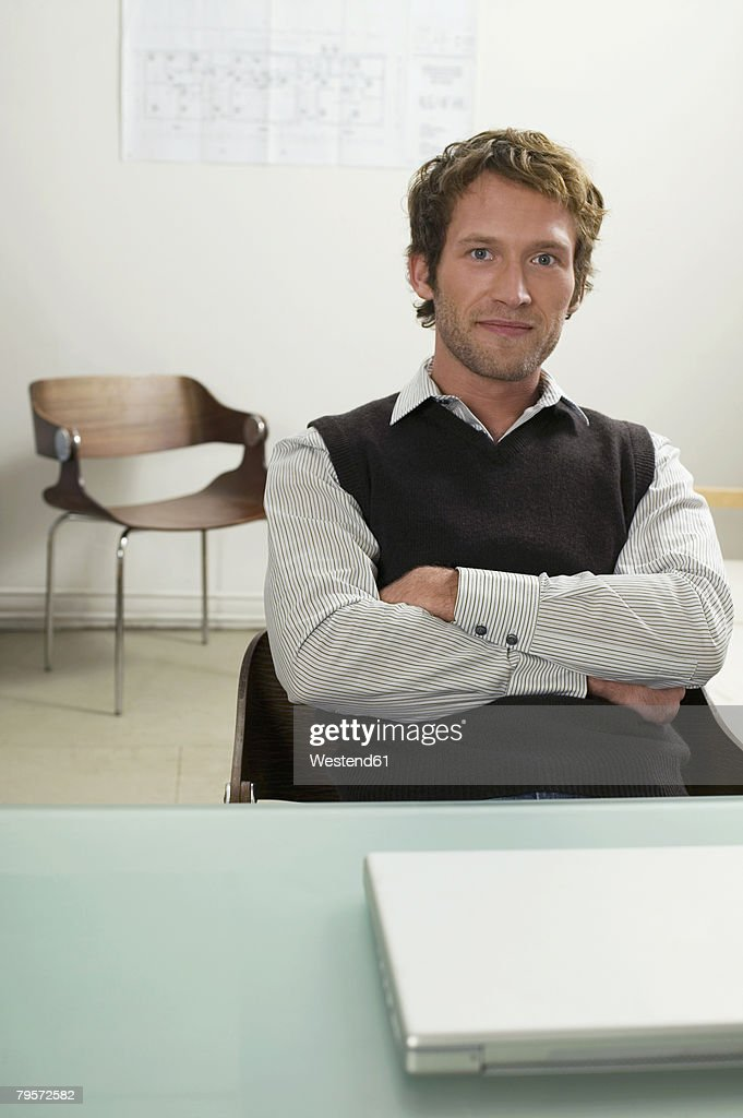 Young Man Sitting On Desk Arms Crossed Stock Photo | Getty Images