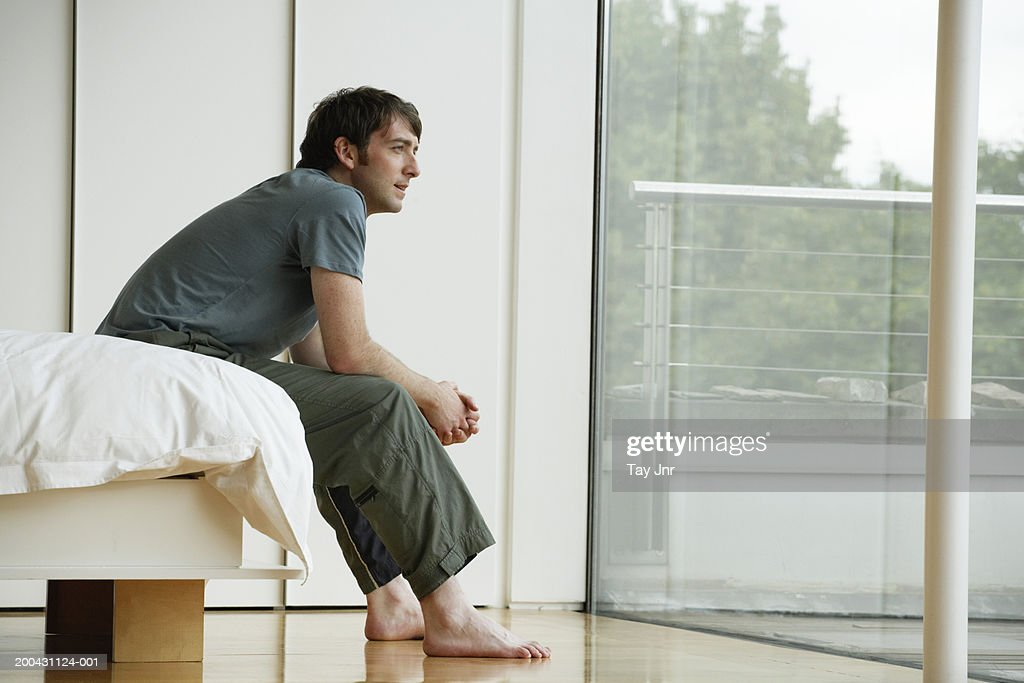 Young man sitting on edge of bed, looking out patio doors, side view : Stock Photo