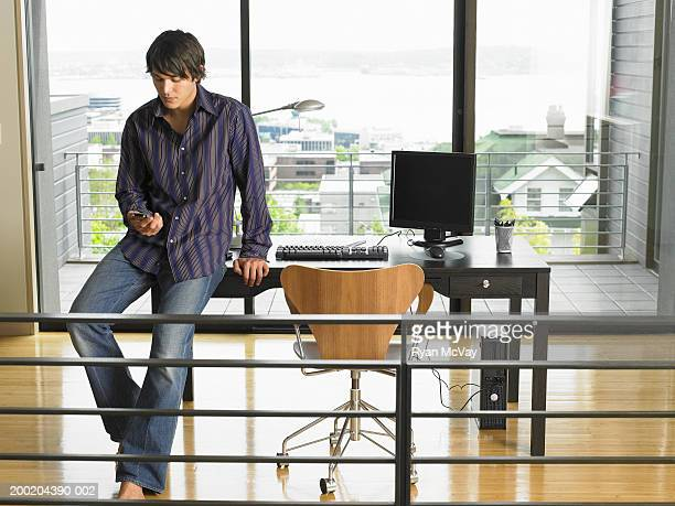 Young man sitting on edge of desk, holding palmtop