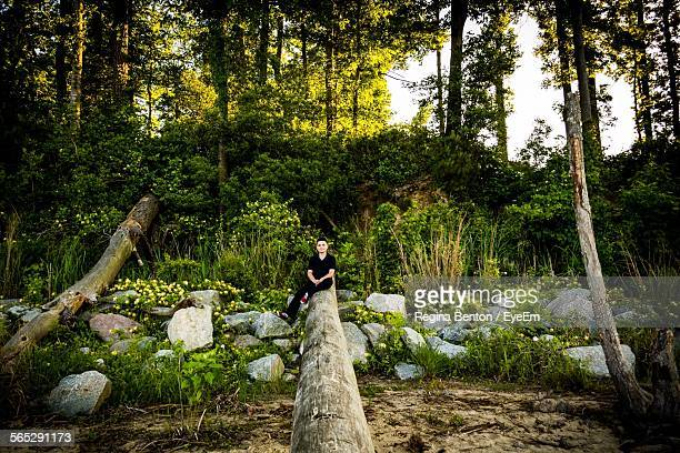 Young Man Sitting On Fallen Tree Trunk In Forest