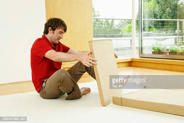 Young man sitting on floor holding flat-pack furniture box, side view