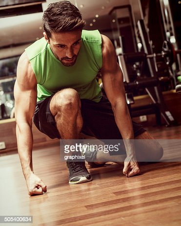 Young Man Sitting on Floor in Gym