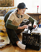 Young man sitting on floor looking through records