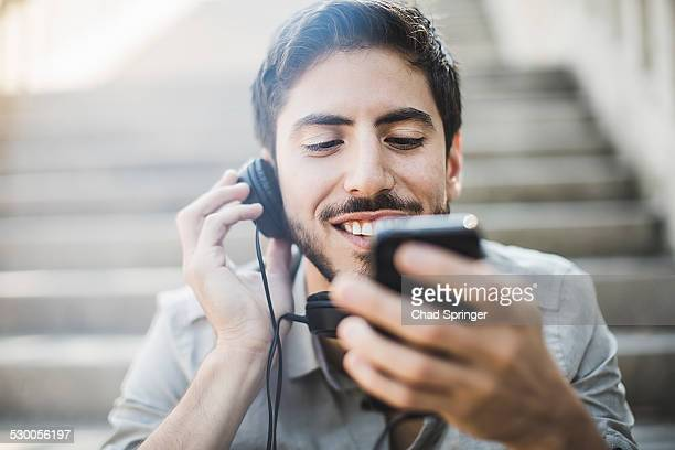 Young man sitting on footbridge stairs listening to music on headphones