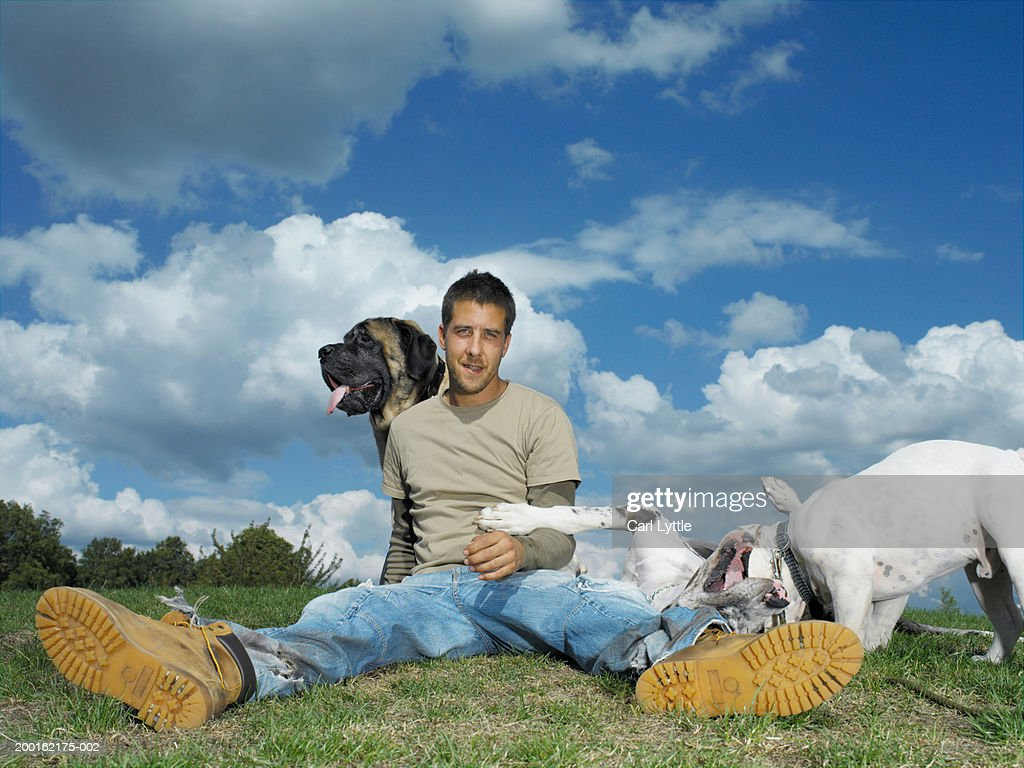 Young man sitting on grass with dogs, portrait : Stock Photo