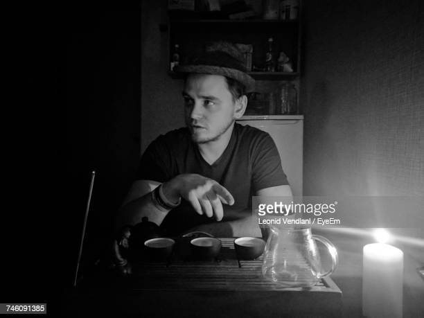 Young Man Sitting On Illuminated Dinning Table At Home