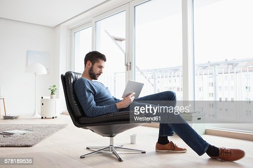 Young man sitting on leather chair in his living room using digital tablet