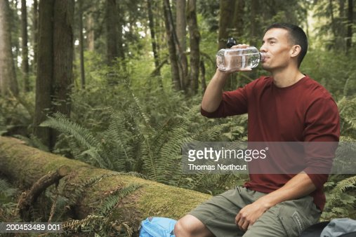 Young man sitting on log in forest, drinking water : Stock Photo