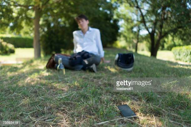 Young man sitting on meadow in park with cell phone away from him