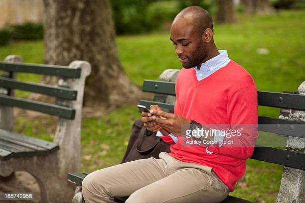 Young man sitting on park bench using mobile phone