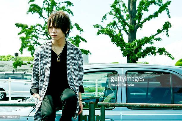 Young man sitting on railing in frond of car