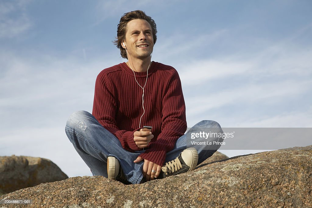 Young man sitting on rock listening to headphones, outdoors : Stock Photo