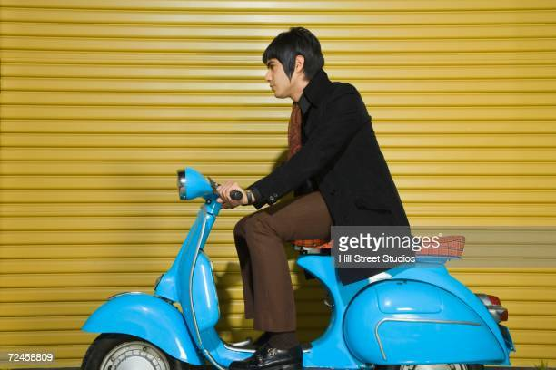 Young man sitting on scooter