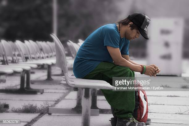 Young Man Sitting On Seat