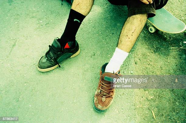 Young man sitting on skateboard wearing different shoes and socks