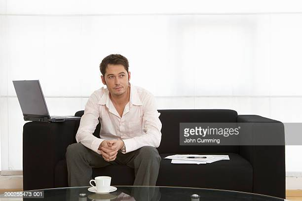 Young man sitting on sofa by tea cup and laptop
