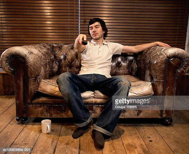 Young man sitting on sofa, holding remote control