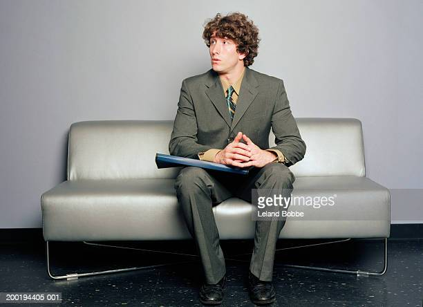Young man sitting on sofa, looking off to side