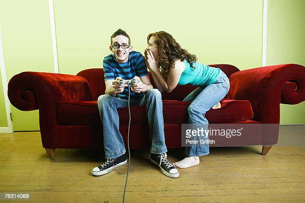 Young man sitting on sofa playing video games, young woman yelling