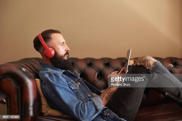 Young man sitting on sofa using digital tablet