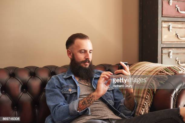Young man sitting on sofa using smartphone