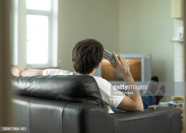 Young man sitting on sofa watching television, rear view