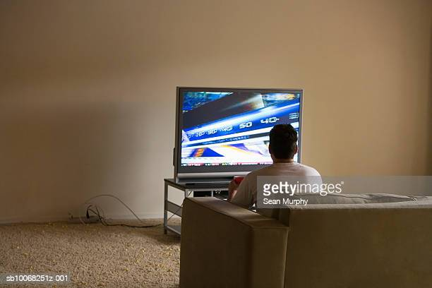Young man sitting on sofa watching tv, rear view